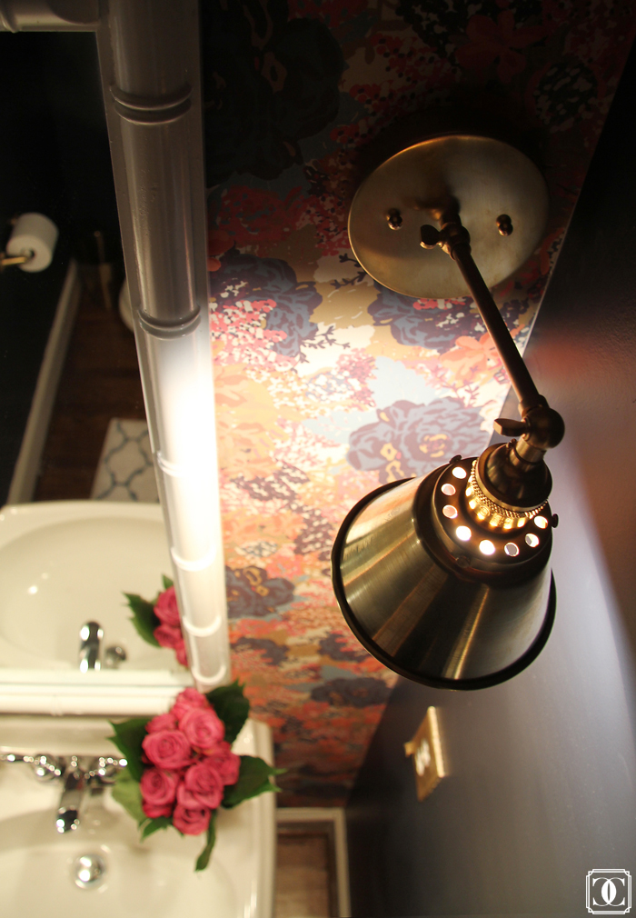brass lighting, floral wallpaper, bamboo mirror, navy walls