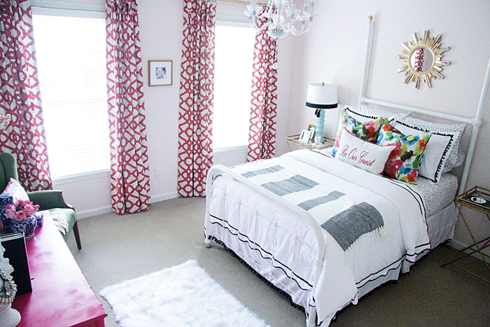 guest room decor, colorful bedding, colorful drapes, x-table, white fur rug, sunburst mirror, bamboo dresser