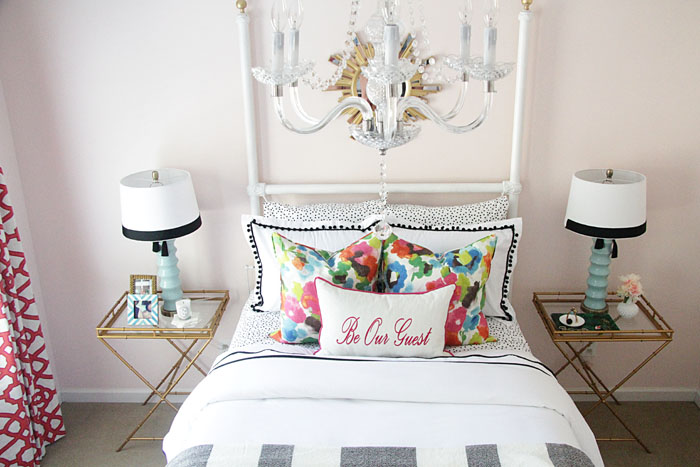 guest room decor, black and white bedding, colorful pillows, blue lamps, colorful drapes, gold sunburst mirror, chandelier