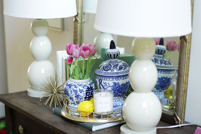 entry way, brass bamboo tray, blue and white ginger jars, white lamps, gold urchin