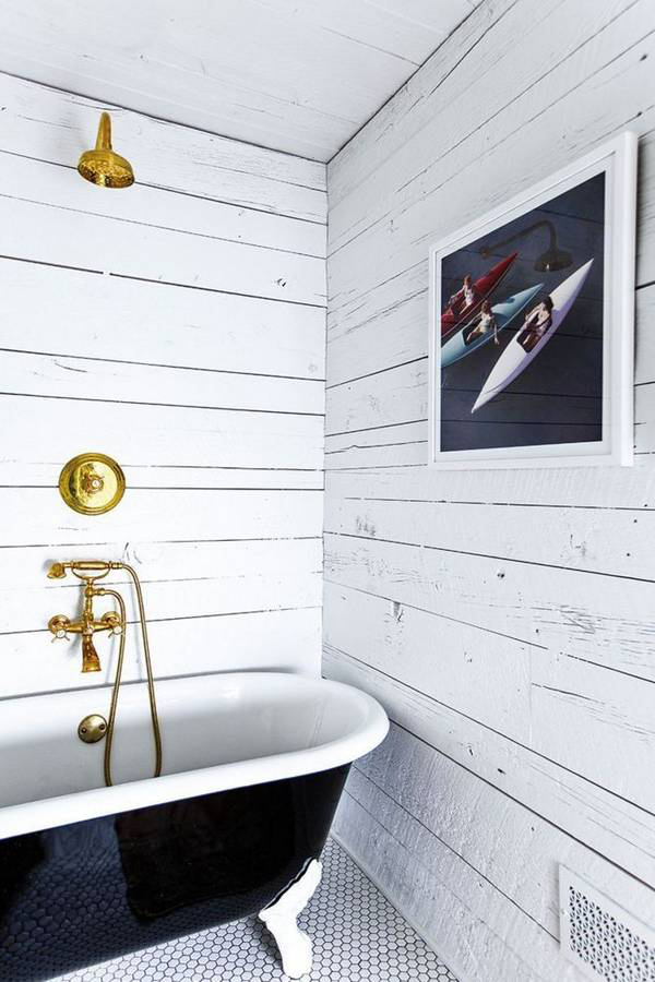 The shiplap walls in this bathroom add the perfect mix of rustic to the glam gold fixtures.