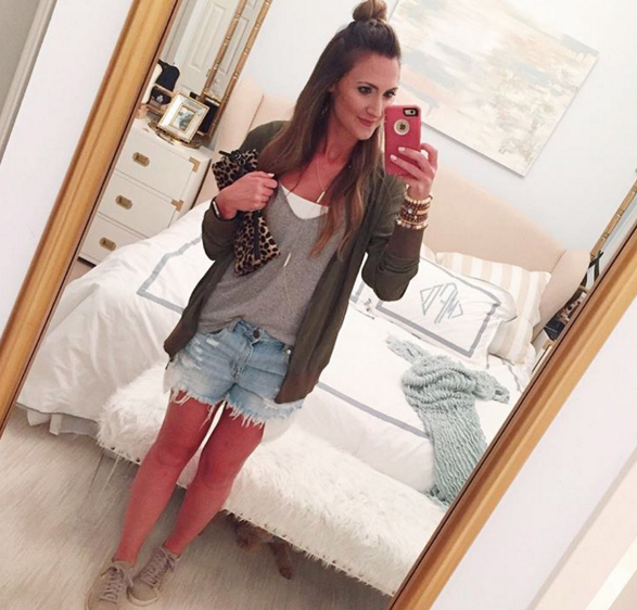 Green bomber jacket with denim shorts for a causal outfit