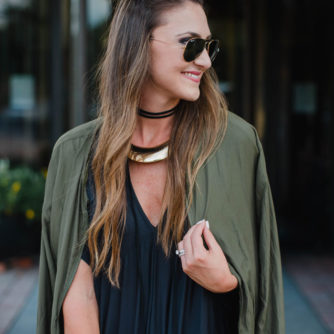 Blogger Mallory Fitzsimmons of Style Your Senses is wearing a chic black shift dress with arm green bomber jacket for a great Fall transition look.
