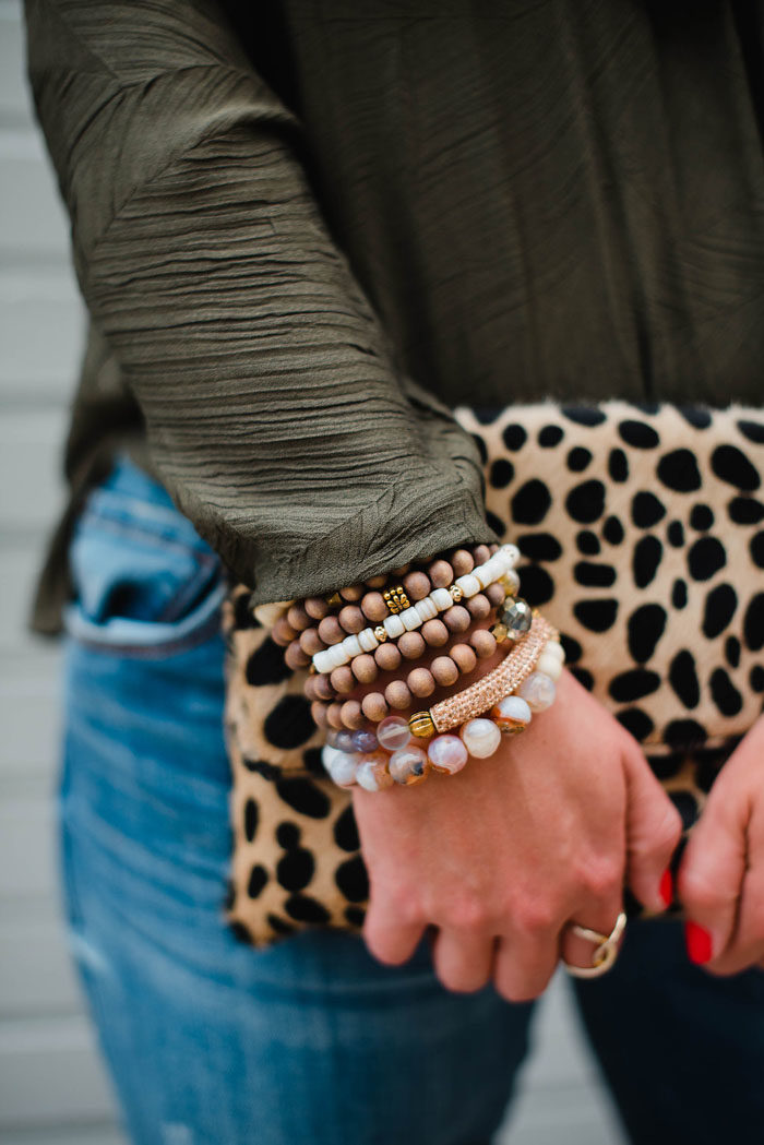 Cooper and Ella crossover top styled with beaded bracelets and a cheetah clutch