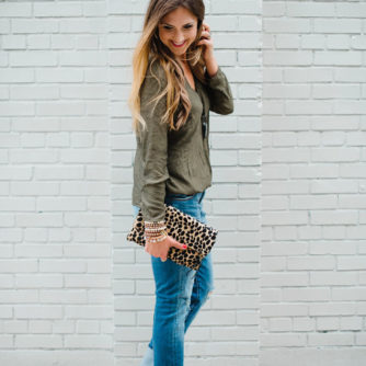 Blogger Mallory Fitzsimmons of Style Your Senses styles distressed boyfriend jeans with a Cooper and Ella crossover top and a cheetah clutch.