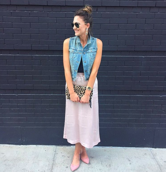 Pink silk skirt paired with a denim vest for a girly and glam look that's still comfortable.