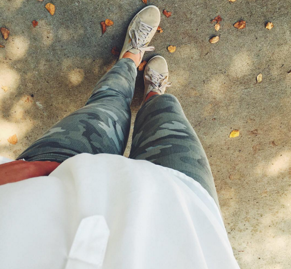 Camo skinny jeans with sneakers and an ivory tunic