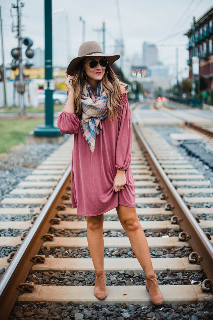 Blogger Mallory Fitzsimmons of Style Your Senses wears a rose pink off the shoulder dress with a felt hat, blanket scarf and Dolce Vita ankle booties