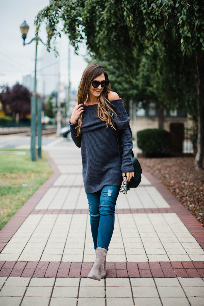 Blogger Mallory Fitzsimmons of Style Your Senses wears an off the shoulder sweater and grey mid calf booties for a transitional outfit.