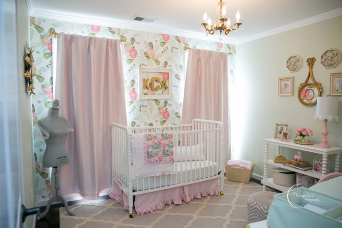 Beautiful baby girl nursery with pink drapes, floral wallpaper, classic Jenny Lind crib and trellis rug