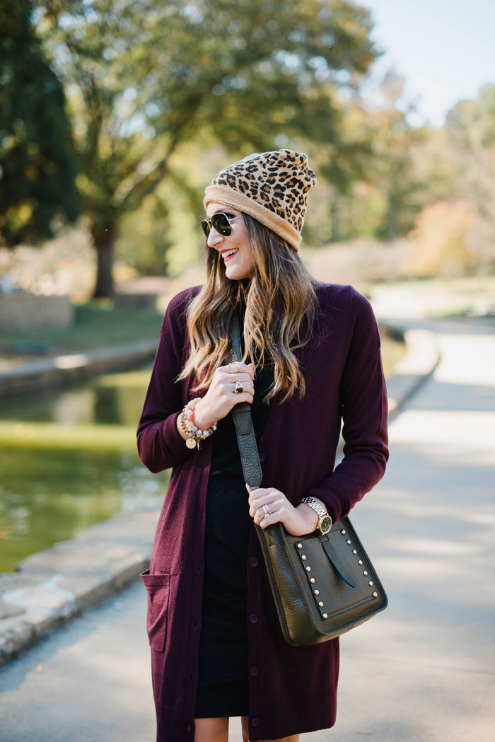 Blogger Mallory Fitzsimmons of Style Your Senses wears a black body con dress layered with a tunic cardigan and Rebecca Minkoff crossbody bag