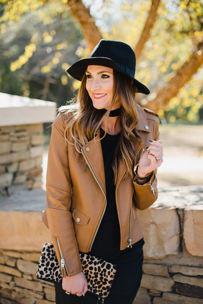 Blogger Mallory Fitzsimmons of Style Your Senses wears a black body con dress with a gorgeous leather moto jacket, felt hat and choker for a dressed up Fall transition look.