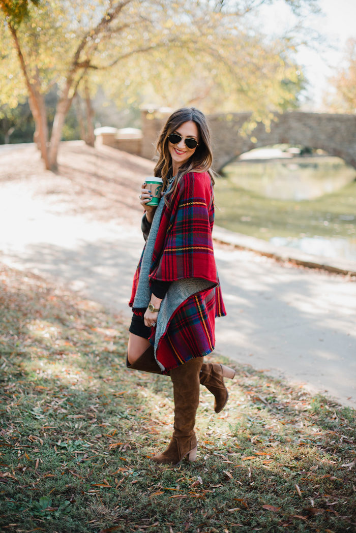 Blogger Mallory Fitzsimmons of Style Your Senses wears a black body con dress as a base layer and a gorgeous reversible poncho over it, finished with chestnut over the knee boots