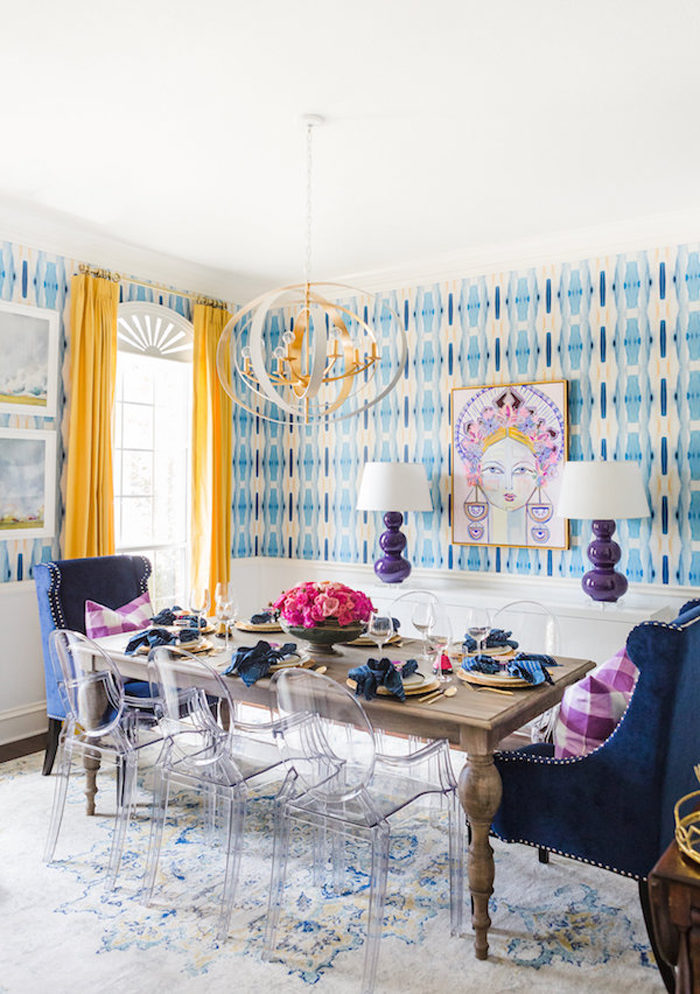 Gorgeous dining room with bold wallpaper, yellow drapes, and custom artwork
