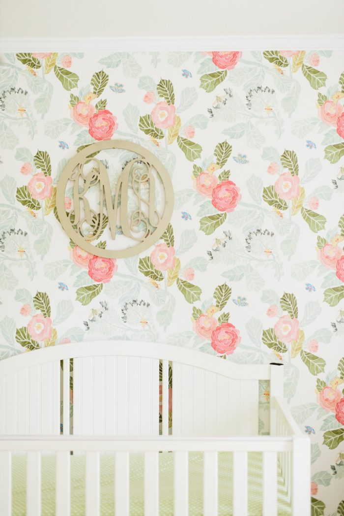 Beautiful baby girl nursery with floral wallpaper from Anthropologie and gold monogram over the crib