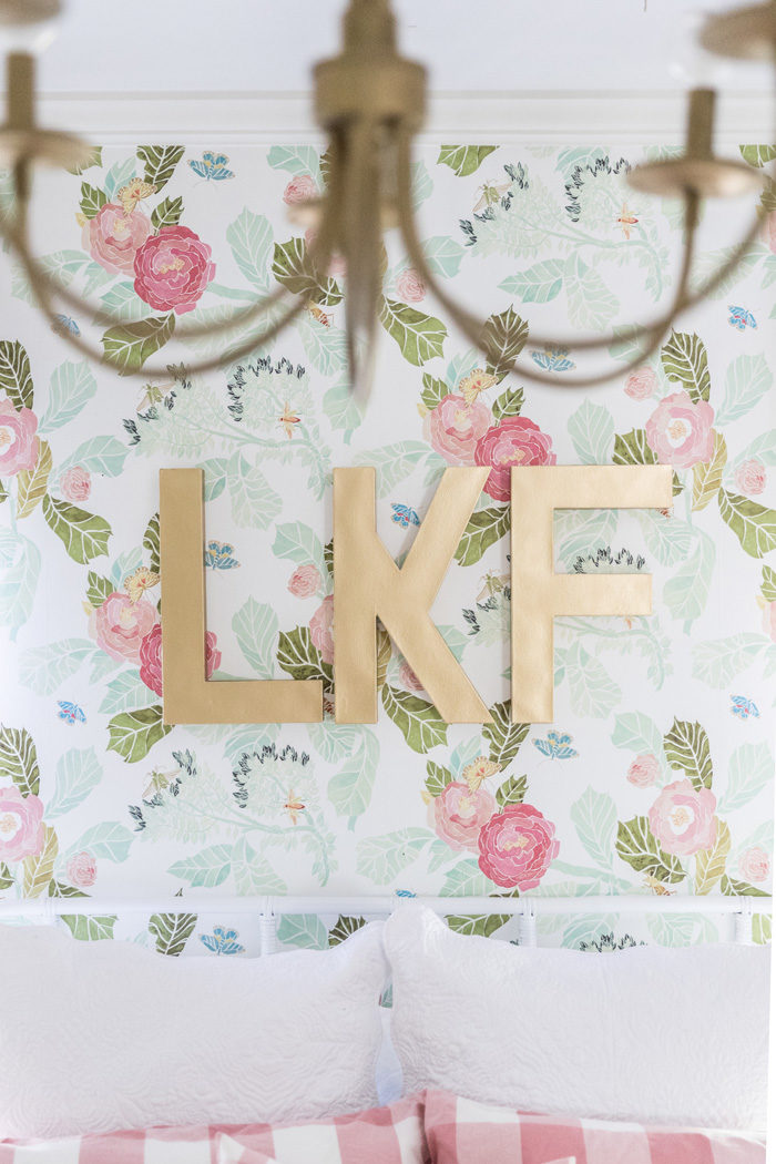 Bold gold monogram against girly floral wallpaper in a girls room