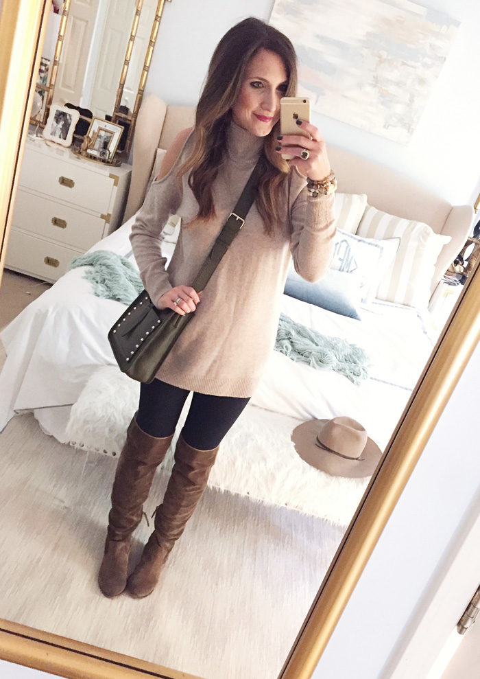 Blogger Mallory Fitzsimmons of Style Your Senses wears a cold shoulder tunic sweater with a large statement necklace, skinny jeans and over the knee boots for a festive Thanksgiving outfit idea
