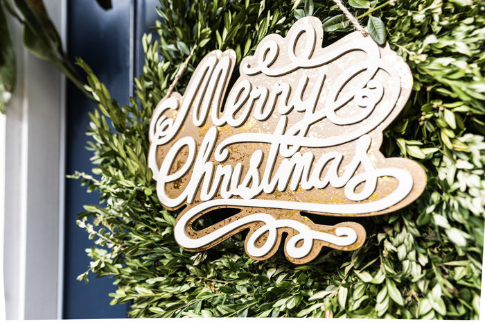 Blogger Mallory Fitzsimmons of Style Your Senses shares her Holiday Home Tour that includes this boxwood front door wreath with wooden Merry Christmas sign - Our Holiday Home Tour featured by popular Texas lifestyle blogger, Style Your Senses