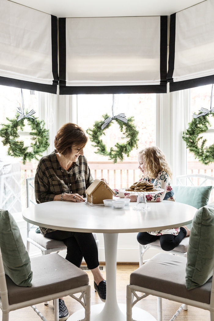 Holiday Home Tour 2016 decorating a gingerbread house in breakfast nook - Our Holiday Home Tour featured by popular Texas lifestyle blogger, Style Your Senses