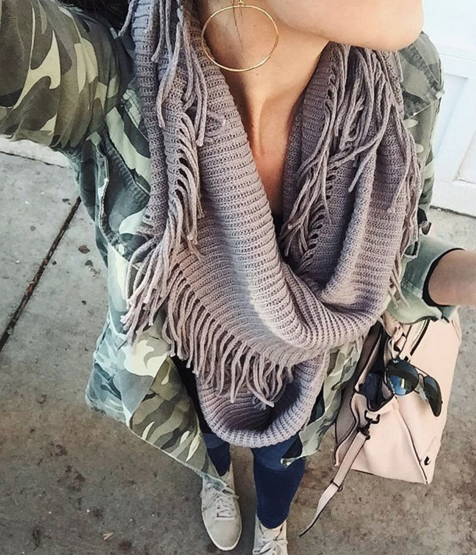 A casual outfit idea layering an infinity scarf, camo jacket and sneakers for a comfortable look that's also chic