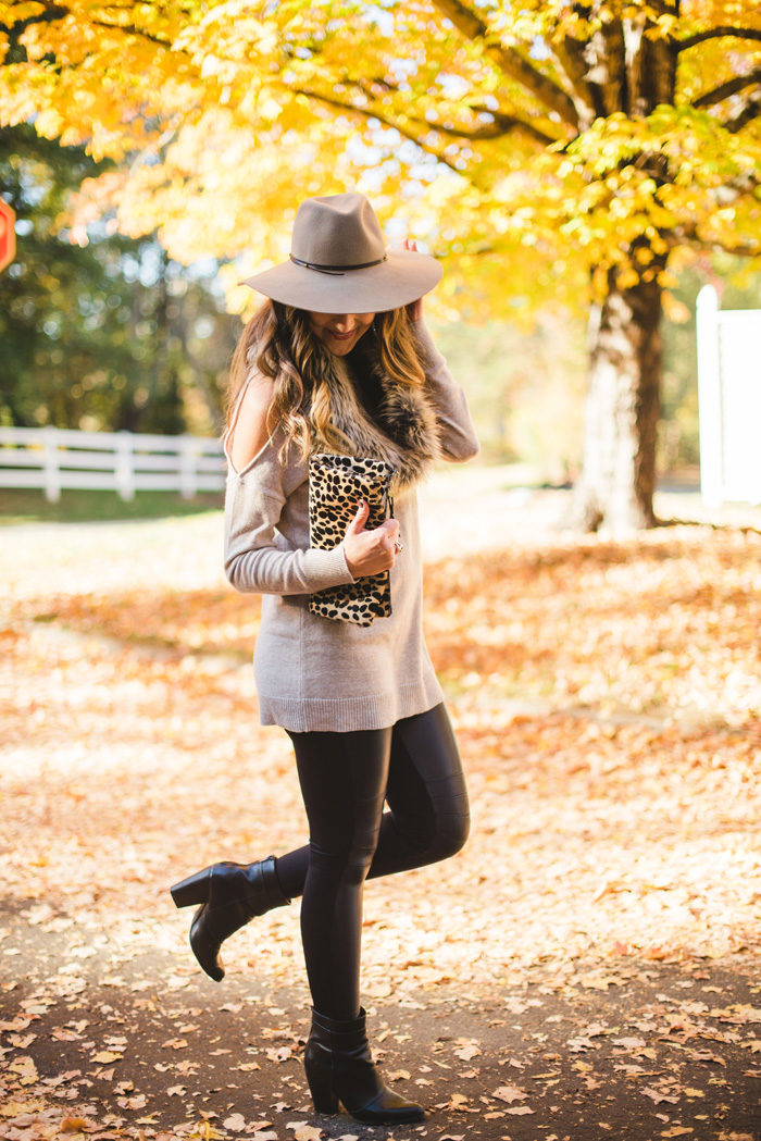 Blogger Mallory Fitzsimmons of Style Your Senses wears a cold shoulder tunic sweater with faux leather leggings, a faux fur infinity scarf and felt hat for a festive Fall and Winter look.